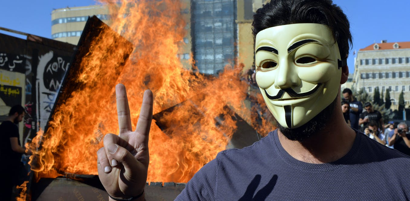 A protester wearing a Guy Fawkes mask flashing a victory sign in Beirut in November 2019. EPA-EFE/WAEL HAMZEH EPA-EFE/WAEL HAMZEH/CO'D